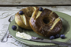 Two blueberry pretzel bagels with butter on knife on a plate. royalty free stock photos
