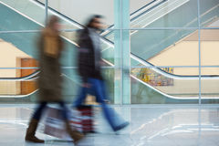 Two Blurred Commuters Walking Along Modern Corridor in Motion Bl Stock Photos