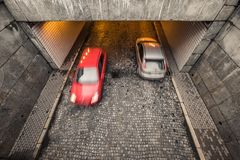 two blurred passanger cars, red and silver, on cobble street in royalty free stock photography