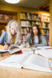 Two blurred students writing notes at library desk Royalty Free Stock Photography
