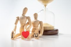Two blurred wooden figure lovers with the letter of I love you on sole of foot. Closeup of Miniature wooden mannequin couple holding each other with red heart stock photo