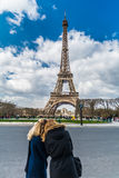 Two blurry blonde tourist girls silhouette over Eiffel tower in Paris Stock Photography