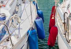 Two boats anchored at the  harbor. Detail of two boats anchored with the typical colored fenders Stock Image