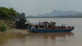 Two boats anchored near the shore. A hand held, long shot of two small, old boats anchored near the shore where the sand meets the green and lively vegetation stock video