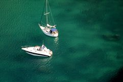 Two boats anchored up. In translucent green sea Royalty Free Stock Photo