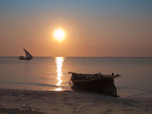 Two boats on a background of the sky with the sea. One boat stand at the shore and the second boat floats against the sunset Stock Image
