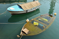 Two boats on berth, one is sinking. Two boats on berth, plastic blue one, and wooden one is sinking Stock Photo