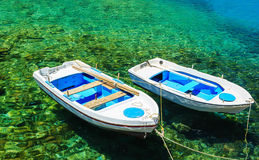 Two boats at the dock in the clear water, which can be seen the bottom and stones Royalty Free Stock Photo