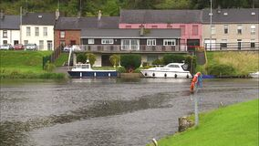 Two boats are docked in front of a house. In an Irish canal. Several houses can be seen behind this one and the other canal bank in the foreground stock video