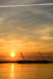 Two boats docking early in the morning near the pier. Horizontal. View of a couple of boats loading up cargo in a summer morning over a sunrising sky on royalty free stock photos