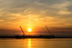 Two boats docking early in the morning near the pier. Horizontal. View of a couple of boats loading up cargo in a summer morning over a sunrising sky on stock image