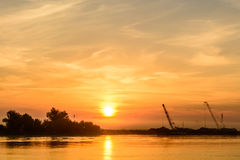Two boats docking early in the morning near the pier. Horizontal. View of a couple of boats loading up cargo in a summer morning over a sunrising sky on royalty free stock photo