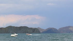 Two Boats Floating In The Sea At Mountains. This is a picturesque shot of two small white boats one of which is sailing while another one is drifting in the stock video footage