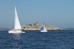 Two boats in front of a red lighthouse - Kornati National Park Royalty Free Stock Photos