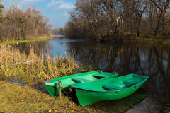 Two boats . Two green  boats on the river bank. Autumn rural landscape - trees are reflected in the water against a blue cloudy sky Stock Photos