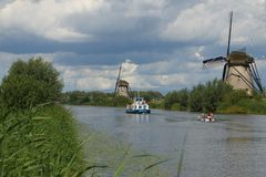 Two boats in kinderdijk the netherlands. Two boats with tourists sail past the windmills in kinderdijk the Netherlands. twee boten met toeristen varen langs de stock image