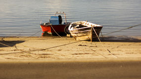 Two boats moored on the beach next to each other Royalty Free Stock Images