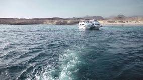 Two boats moored to a deserted island against the background of rocky mountains. In a crystal clear ocean.  stock footage