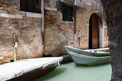 Two boats in the narrow channel of water a milky green. Royalty Free Stock Photo