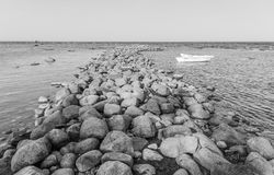 Two boats at the rocky pier. Friendship conceptual image. Two boats on the tranquil sea waiting at the rocky pier. Black and white photo. Friendship conceptual Stock Image