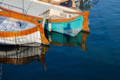 Two boats reflecting in the sea water stock images