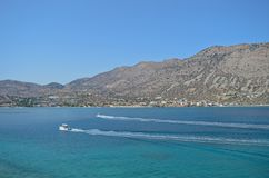 2 boats are passing the historical Spinalonga island in Greece. Two boats are riding on the beautiful blue sea nearby Spinalonga island Stock Photos