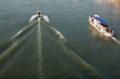 Two boats on the river. Small motor boat passing steam boat on the river royalty free stock photography