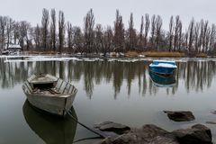 Two boats on the river on a winter morning with reflection in the water royalty free stock images
