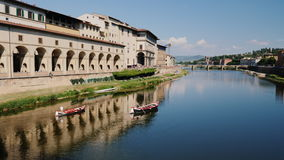 Two boats sail along the Arno River, beautifully reflected in the water. With a view of Florence and the bridges. 4K video stock video footage