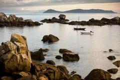 Two boats at sea between rocks Royalty Free Stock Photos