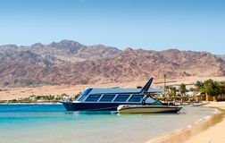 Two boats at the surf on the background of the beach with palm trees and high rocky mountains in Egypt .Sharm el sheikh royalty free stock images