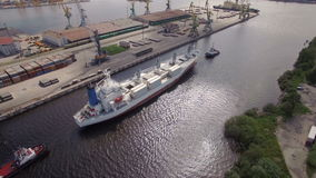 Two boats towing a container ship in channel, aerial view stock video footage
