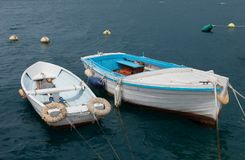 Two boats and wavy sea. Two aged boats, more like dingies, moored, rocking on sea water stock image