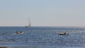 Two Boats And Yacht Sailing In The Sea. In the frame there are two boats run by sailors and one yacht in a distance sailing in the Black sea at sunny daytime stock video footage