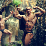 Two bodybuilders posing in a cave Royalty Free Stock Photo