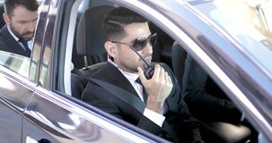 Security team transporting a businessman. Two bodyguards talking over the radio while transporting an important businessman and providing security stock footage