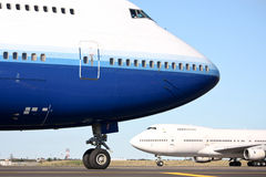 Two Boeing 747 jumbo jets on the runway. Two Boeing 747 jumbo jets cross on the runway Royalty Free Stock Images
