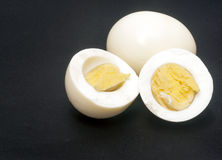 Two boiled eggs. One halved surrounded by black background Royalty Free Stock Photos