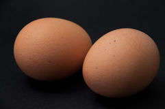 Two boiled eggs on the black background Royalty Free Stock Photos