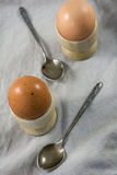 Two boiled eggs in egg cups with spoons. On the linen cloth Royalty Free Stock Photos