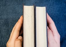 Two books in female hands on a warm, blue plaid stock photo