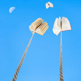Two books tied on ropes soars into blue sky Stock Photo