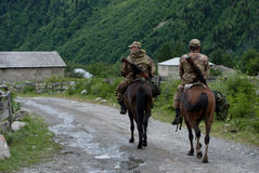 Two border guards on horses in the village Mazeri, which located Royalty Free Stock Images
