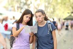 Bored backpackers searching location. Two bored backpackers searching location in a map in the street stock photo