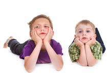 Two bored kids lying on the white Stock Image