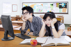 Two bored student studying in the class. Portrait of two high school student sitting in the classroom with bored expression studying together Royalty Free Stock Photo