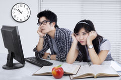 Two bored students studying together. Picture of two college student studying together and looks bored with books and computer on the table Stock Photo