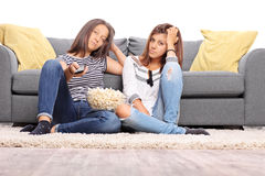 Two bored teenage girls watching TV. And changing the channels isolated on white background Stock Image