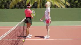 Two bored tennis players standing on court. Two attractive young female friends in short skirts playing with their rackets with bored expressions while waiting stock footage