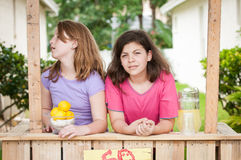 Two bored young girls selling lemonade Stock Images